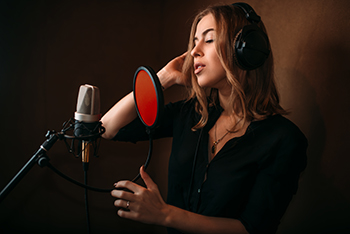 Female singer recording a song in music studio. Woman vocalist in headphones against microphone. Audio recording. Professional digital sound technologies