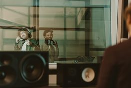 RAD young happy musicians recording song behind glass at studio and